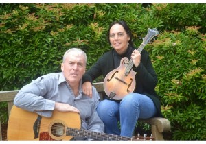 Man and woman sitting against background of trees. Man holds guitar and woman holds smaller guitar.