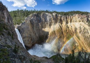 Waterfall and mountains with rainbow arcing over gorge
