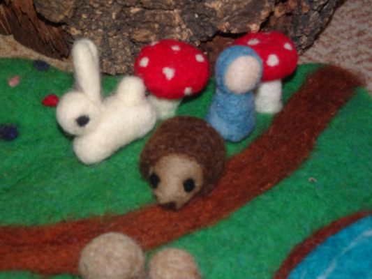 felted garden scene with mushrooms, hedgehog, and bunny