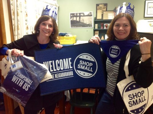 2 women holding up Small Business Saturday items and wearing hats