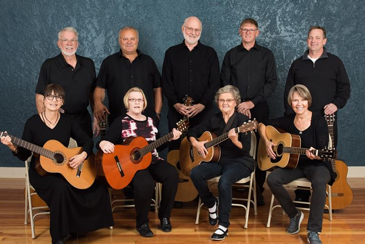Group of people posing for camera holding instruments